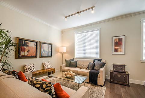 A small, bright living room with beige couches and  indoor plants, near where RL Property Management provides Franklin County property management